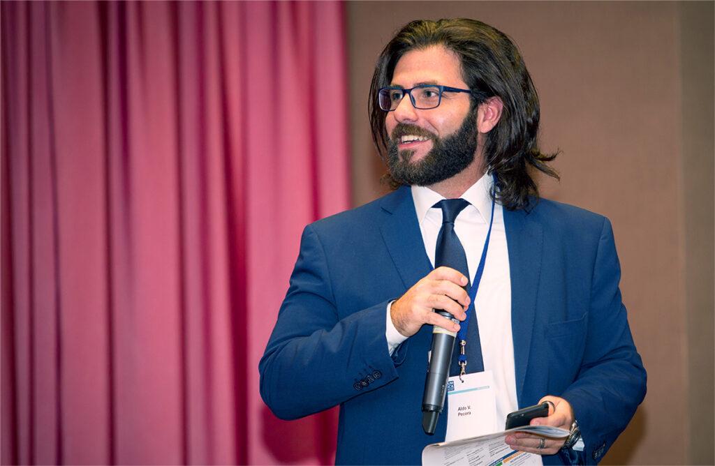 """Il presidente di """"Ammazzateci tutti"""", Aldo V. Pecora durante un evento economico a Milano nel 2018"""